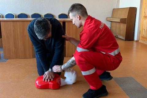 Studentas -paramedikas rodo bendruomenės nariui kaip taisyklingai atlikti žmogaus gaivimą.