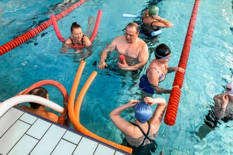 Plaukimo treniruotė baseine Dalyviai mokosi plaukti ir atlieka plaukimo pratimus su plūdurais