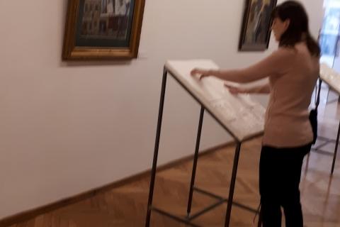 L. Ulinauskaitė apžiūri , neregiams pritaikytą paveikslą.