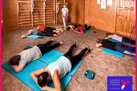 A. Girniūtė veda sveikatingumo treniruotę. Dalyvauja 8 moterys, kurios atleika nugaros raumenų stiprinimo pratimą.